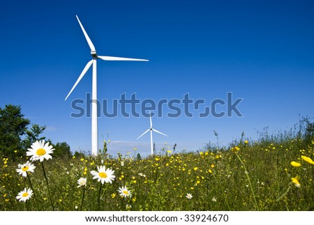 A pair of energy producing wind turbines - windmills - in a field. Complete with green meadow, daisy flowers and blue sky.