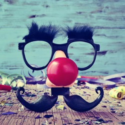 a pair of fake black glasses with eyebrows, a red clown nose and a mustache forming the face of a man on a rustic wooden surface full of confetti