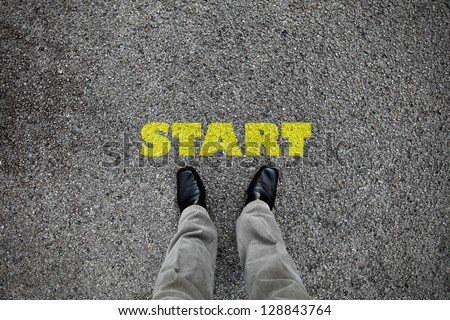 A pair of feet on a tarmac road with yellow print of the word start for the concept of starting point.