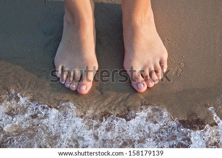 A pair of feet on the beach about to be covered by a wave.