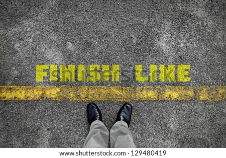 A pair of feet standing at the edge of a yellow line on an asphalt road with a yellow print of the word Finish Line for the concept of accomplishment.