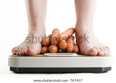 A pair of female feet standing on a bathroom scale with a pile of carrots between them.