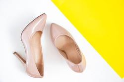 A pair of female shoes of beige boats on a white background. Elegant shoes. View from above. Pumps.