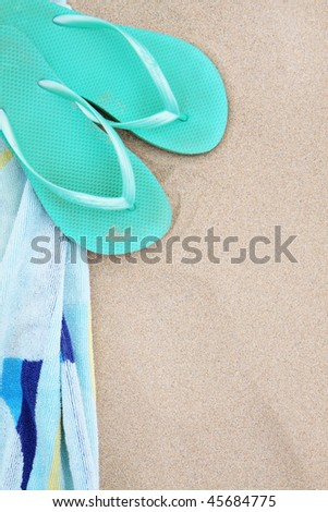 A pair of flip flops and beach towel on the sand.