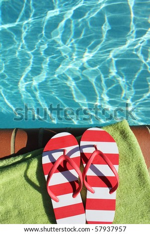 a pair of flip flops at the edge of a swimming pool