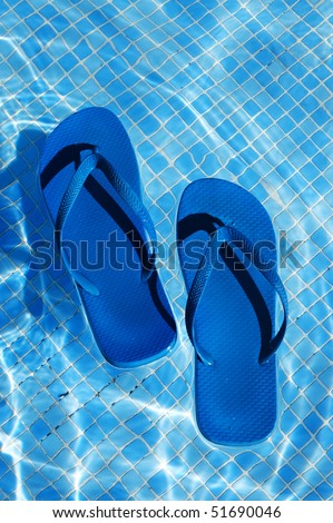 a pair of flip-flops floating on the water on a swimming pool