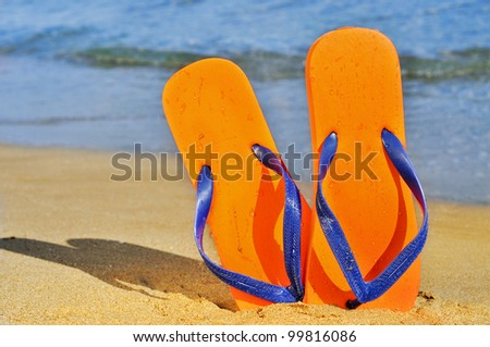a pair of flip-flops on the sand of a beach - stock photo