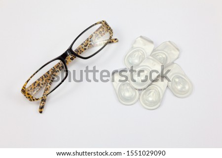 A pair of glasses and a pile of contact lenses - Eyesight Concept