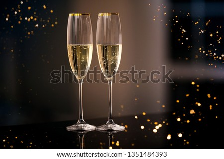 A pair of glasses of champagne in the interior. Festive picture of two wine glasses with sparkling champagne. Closeup of a pair of wine glasses. Dining and night life concept. #1351484393