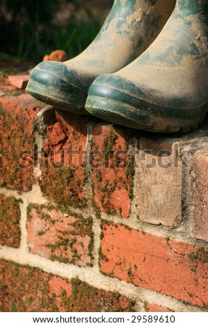 A pair of green muddy wellington/garden boots set atop a red bricked garden wall.