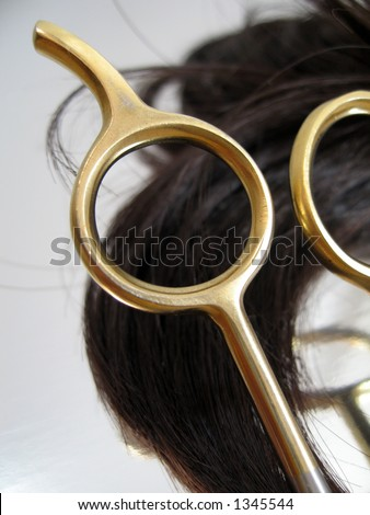 A pair of haircutting scissors and hair on a silver reflective background.