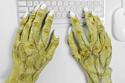 A pair of halloween monster hands using a keyboard and mouse against a white background.