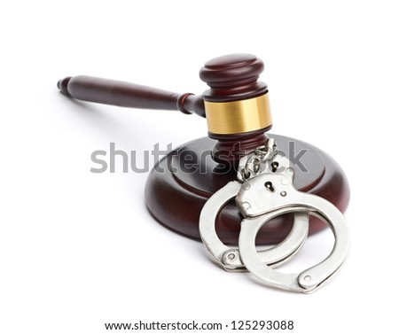 A pair of handcuffs and gavel are isolated for legal concepts.