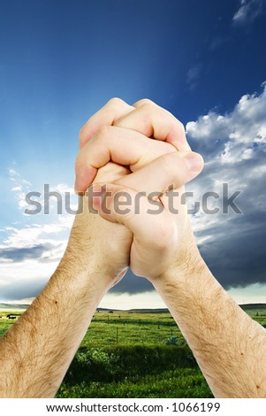 A pair of hands giving thanks on the prairie landscape