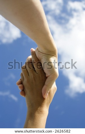A pair of hands holding or shaking each other against a blue sky. Concept: Agreeement reached or helping hand.