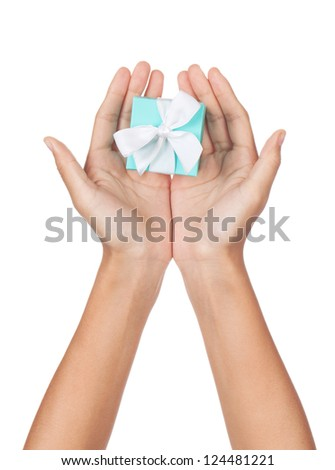A pair of hands with palms open holding a small blue box with a white ribbon isolated on white. - stock photo