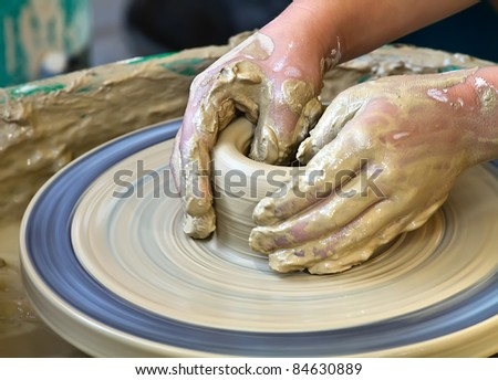 A pair of hands work on pottery