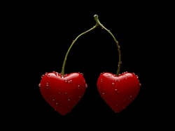A pair of heart shaped cherries isolated on black background