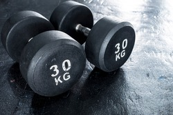 A pair of heavy 30 kilogram dumbbells on rubber floor matting at the gym. Made with cast iron and coated with rubber. Knurling handlebar