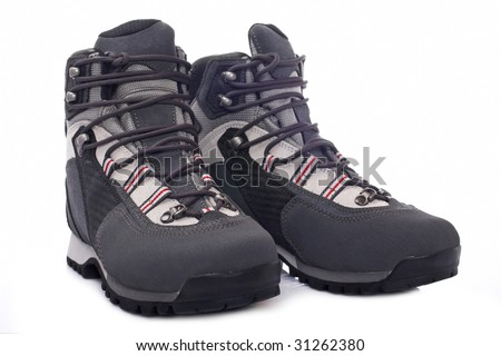 A pair of hiking boots with soft shadow reflected on white background. Shallow depth of field