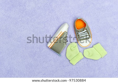 A pair of infant baby shoes and socks on a fluffy purple blanket.