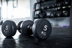 A pair of 5 kilogram dumbbells lying on the floor of a gym, with a dumbbell rack visible in the background.