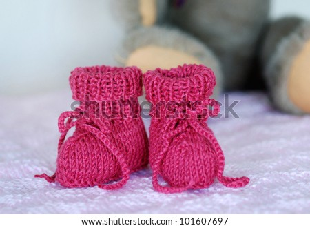 A pair of knitted, bright pink baby booties