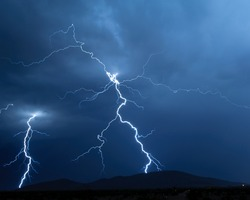 A pair of lightning bolts twisting through the air on their way down to a mountain near Arlington Arizona during the 2012 Monsoon season.