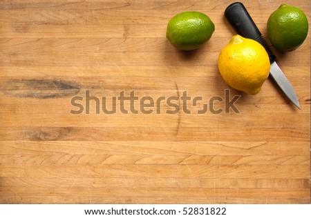A pair of limes and a lemon wait to be cut on a worn butcher block cutting board