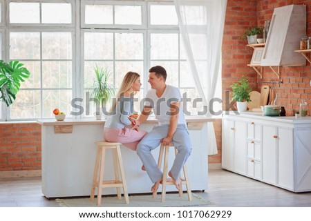 A pair of lovers having breakfast in the kitchen / A girl looks at the guy and smiling / the concept of relations #1017062929