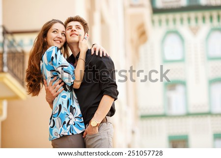 A pair of lovers people on the city walk. The love story of two young people. Man and woman embracing each other. Walking through the city summer day. Feelings of love between two people. Love story.