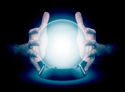 A pair of male hands surrounding a crystal ball conjuring up a hologram on an isolated dark studio background