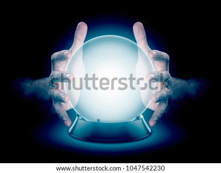 A pair of male hands surrounding a crystal ball conjuring up a hologram on an isolated dark studio background #1047542230