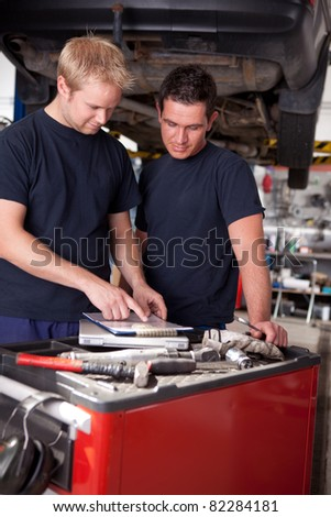 A pair of mechanics working on a car looking a service order