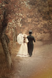 A pair of men in a black tailcoat hat and a woman in a beige hat, in a dress, with an umbrella. They walk along a park path with backs to the camera.