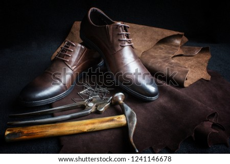 A pair of men's classic brown shoes and leather shoemaking tools