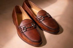 A pair of men's leather bit loafers in the sunlight during a fashion indoor photoshoot.