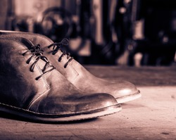 A pair of men's leather shoes in the shoemaker's workshop on working desk.Monochrome cream tone. Black and white photography.