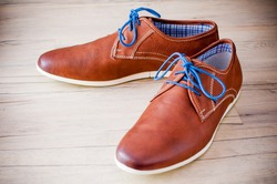 A pair of men's leather shoes with colorful laces placed on wooden floor