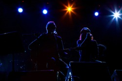A pair of musicians playing music on stage