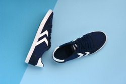 A pair of navy blue sneakers lying on a dark and light blue background. Minimal photo