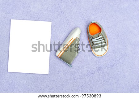 A pair of new baby boy tennis shoes on a purple blanket with blank white card for placement of copy - stock photo