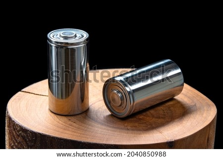 A pair of new modern high-capacity lithium-ion cells. A prototype of new batteries on a tree stump on black background Zdjęcia stock ©