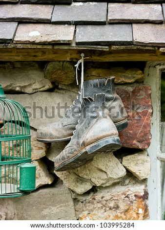A pair of old black leather boots hanging from a nail outside an old stone cottage.