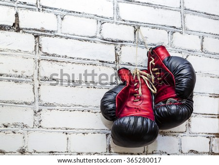 A pair of old boxing gloves hanging on white brick wall background. Zdjęcia stock ©