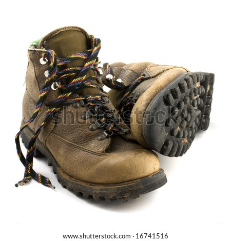 a pair of old, well-worn, hiking boots, brown with colorful laces and some mud, isolated on white