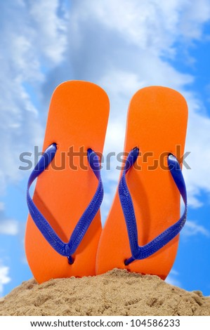 a pair of orange flip-flops on the sand over the blue sky