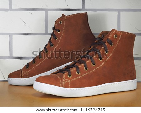 A pair of orange sneakers close up on the light brown exhibition shelf and white brick background.