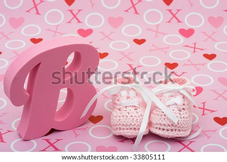 A pair of pink baby booties and the letter B on a pink love background, pink baby booties