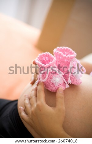 A pair of pink color baby booties on pregnant motherâ??s belly. This picture was taken at home, 3 weeks before due date. Natural lighting.